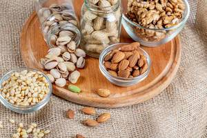 Almonds, pistachios, pine nuts and walnuts on a wooden kitchen board with burlap