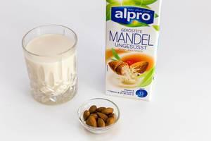 Alpro Mangelmilch, ungesüßt, in der Verpackung, neben einem Glas vegane Milch und einer kleinen Schüssel mit ganzen Mandeln
