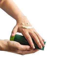 Als lachendes Gesicht aufgetragene Handcreme auf Frauenhänden, die Tube halten