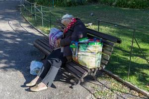 Alte Frau schläft auf einer Parkbank