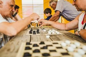Alte Männer spielen Schach und andere Brettspiele gegeneinander