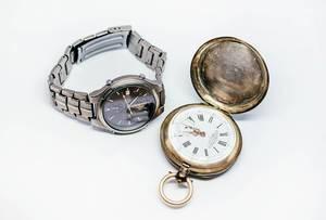Alte Taschenuhr und moderne Armbanduhr aus Titanium vor weißem Hintergrund