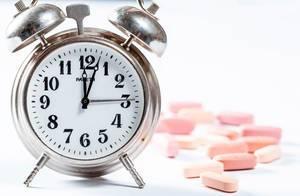 Alter Wecker aus Metall neben rosaroten Tabletten mit Schärfentiefe vor weißem Hintergrund