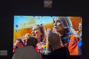 Ältere Messebesucher schauen sich einen 8K Fernseher aus der Nähe an