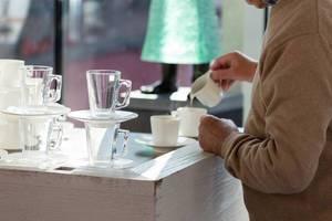 Älterer Herr gießt Milch in seinen Kaffee