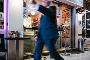 Älterer Mann im Anzug läuft an einem Café und offener Fast-Food Bar in Athen, Griechenland, vorbei