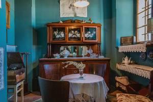 Altes Familien-Esszimmer mit Büffetschrank und bestickter Tischdecke