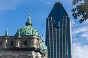 Altes, historisches Gebäude neben einem modernen Wolkenkratzer vor blauem Himmel