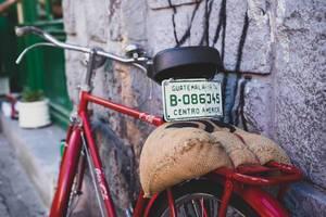 Altes ,rotes Fahrrad mit Nummernschild aus Guatemala und Jutesack lehnt an Steinmauer