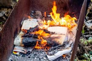 Altes Zeitungspapier in einem Feuer