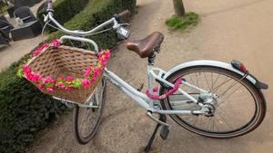 Altmodisches Fahrrad mit einem geflochtenen Korb mit Blumen