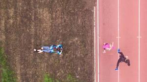 Am Bauch liegende Fotografin fotografiert Läuferinnen