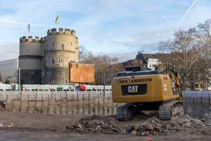Am Kölner Rudolfplatz hebt Raupenbagger Baugrube aus