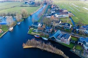Am Wasser erbaute Häuser mit Booten in Akmarijp, Niederlande