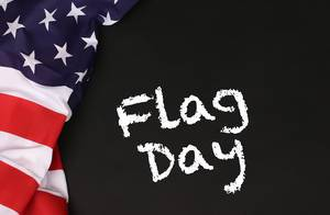 American flag with the text Flag day against a blackboard background.jpg