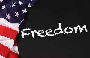 American flag with the text Freedom against a blackboard background