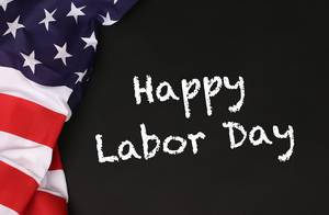 American flag with the text Happy Labor Day against a blackboard background