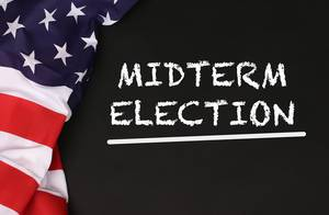 American flag with the text Midterm Election against a blackboard background