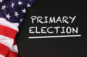 American flag with the text Primary Election against a blackboard background