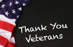 American flag with the text Thank You Veterans against a blackboard background