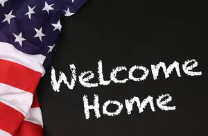 American flag with the text Welcome Home against a blackboard background