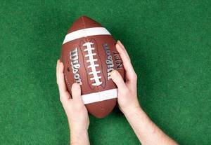 American football player holding up football ball