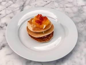 American Pancakes gestapelt mit einer Scheibe Orange und Roter Konfitüre auf einem weißen Teller