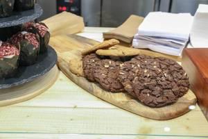 Amerikanische Cookies mit Schokolade und Muffin-Tulpen aus frischem Mett, in einem katalonischen Café am Camp Nou Stadion in Barcelona, Spanien