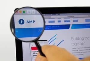 AMP-Logo am PC-Monitor, durch eine Lupe fotografiert