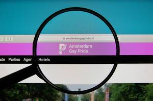 Amsterdam Gay Pride website on a computer screen with a magnifying glass