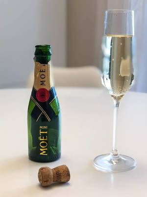 An empty bottle of Mini Moët, a full glass of Champagne and a cork on a white table