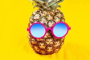 Ananas trägt runde Sonnenbrille vor gelbem Hintergrund