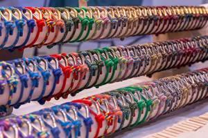 Aneinandergereihte farbenfrohe Armbänder für Bootfans aus Tauen und Ösen auf rundem Holz