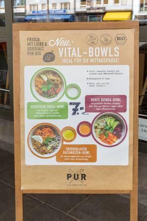 Angebotstafel vor einem deutschen Restaurant der Bio-Manufaktur PUR, mit veganen Vital-Bowls-Gerichten