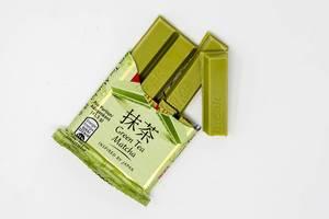Angebrochene Schokoriegel in grüner Farbe und japanischem Grünen Matcha Tee Geschmack, isoliert auf weißen Untergrund