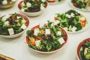 Angerichtete Schalen mit grünem Salat, Tomate und Fetakäse auf weißem Tischtuch