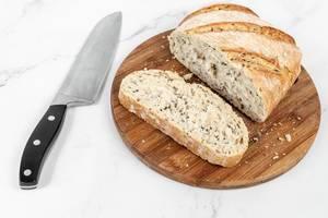 Angeschnittenes, rustikales Brot und Brotscheibe auf einem Holzbrettchen