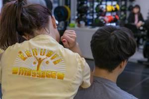 Angestellte von Renuova Massage aus Arizona, USA massiert Besucher der Fibo Gesundheitsmesse in Köln
