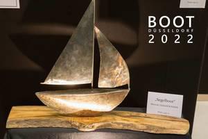 """Angestrahltes Kunstwerk auf einem Holzstamm zeigt ein Segelboot aus Edelstahl und Robinie, neben dem Bildtitel """"Boot Düsseldorf 2022"""""""