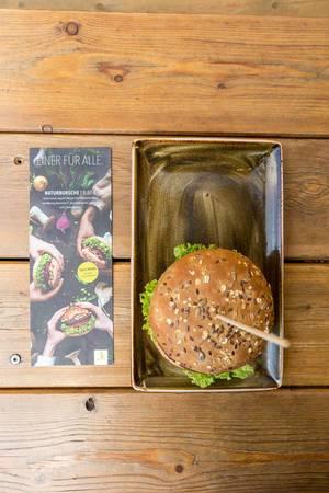 """Ansicht von oben auf den neuen veganen Burger mit Pflanzenbratling von Moving Mountains mit karamellisierten Zwiebeln bei """"Hans im Glück"""""""