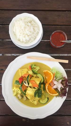 Ansicht von oben auf ein asiatisches, fleischloses Gericht mit ausgewogenem Gemüse und Orange in einer veganen Curry-Kurkuma Sauce, neben Reis