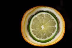 Ansicht von oben auf eine geschnittene Limone, Zitrone und Orange, ineinander gestapelt