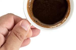 Ansicht von oben auf eine Tasse mit schwarzem Kaffee in einer Hand, vor weißem Hintergrund