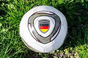 Ansicht von oben auf einen Fußball in der Nahaufnahme, mit deutscher Flagge