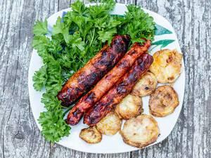 Ansicht von oben auf frittierte Zucchinischeiben, drei Grillwürstchen und frischen Kräutern, auf einem alten Holztisch