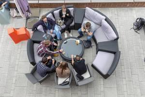 Ansicht von oben auf Menschen auf der runden Terrassen-Couch der Veranda des AXA-Gebäudes, Teilnehmer des Barcamp OMWest 2019 in Köln