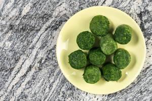 Ansicht von oben auf Teller mit Portion Spinat als tiefgekühlte Würfel auf Marmorplatte