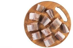 Ansicht von oben auf ungebratene Hechtstücke auf Küchenbrett aus Holz vor weißem Hintergrund