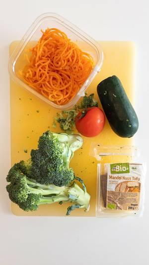 Ansicht von oben auf vegan Zutaten für ein ausgewogenes Mittagessen, mit Brokkoli, Tomate, Zucchini, Möhrenspaghetti und Mandel-Nuss-Tofu