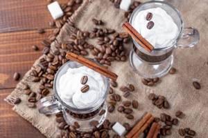 Ansicht von oben auf zwei Gläser mit Kaffee und Sahne, verziert mit Kaffeebohnen und Zimtstangen, auf einem Leinentuch